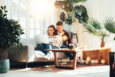Young couple sitting on a sofa looking at mortgage holidays on their laptop