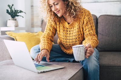 Lady sitting on her sofa looking at her laptop and information about Mortgage market makes 'astonishing' recovery